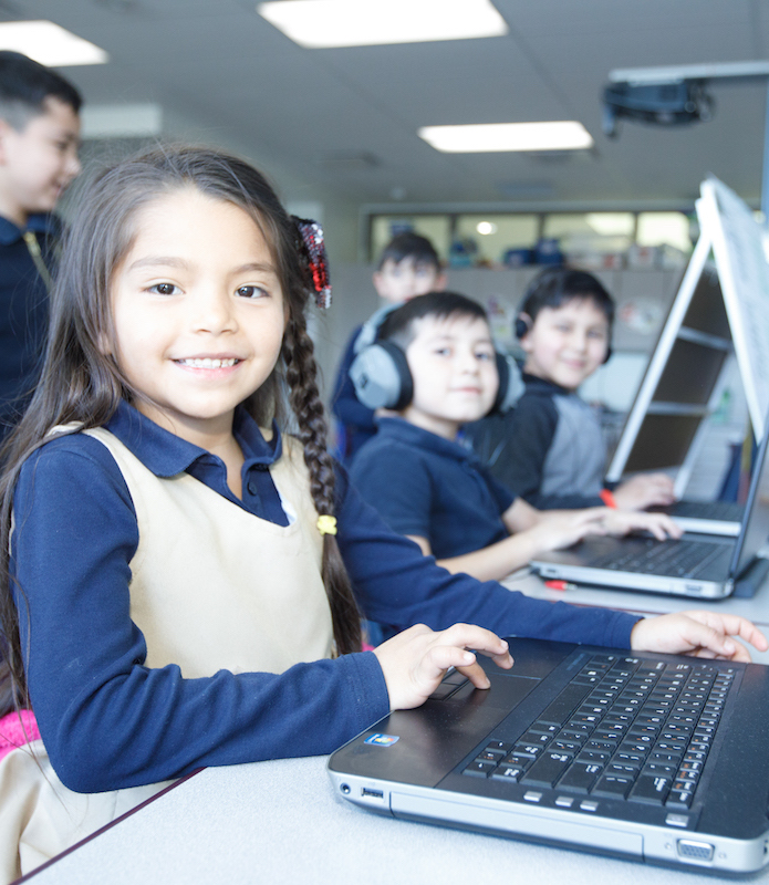 Students smile while using laptops.